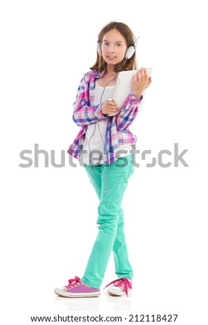 Little girl in headphones holding a digital tablet and looking at camera. Full length studio shot isolated on white. - stock photo