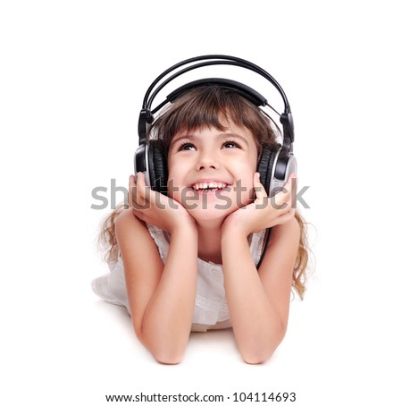 Little girl in headphones listening to the music and looking to the copy space area - stock photo