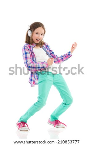 Little girl in headphones playing the air guitar and singing. Full length studio shot isolated on white. - stock photo