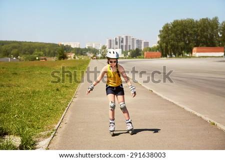 Little girl in helmet on the skates. sports child rollerskating outdoors - stock photo