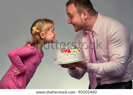 Little girl in her birthday with her father - stock photo