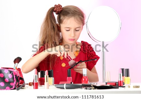 little girl in her mother's dress, is trying painting her face - stock photo