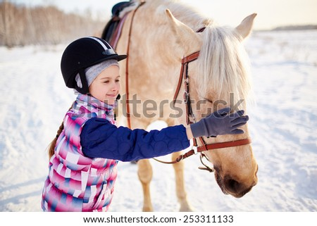 Little girl in jockey helmet touching horse muzzle - stock photo