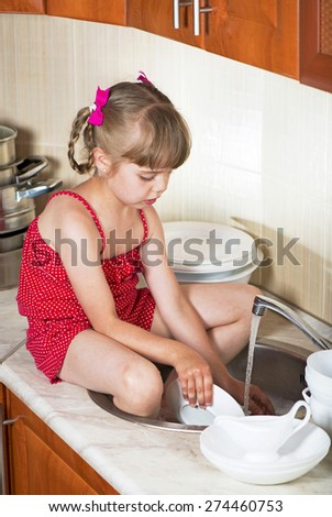 little girl in kitchen washes the dishes - stock photo