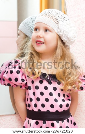 Little girl in knitted hat looking at mirror - stock photo