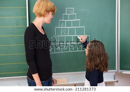 Little girl in mathematics class standing completing a chart on the blackboard watched by a smiling young female teacher - stock photo