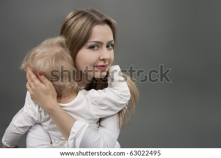Little girl in mother's arms seeking protection and comfort - stock photo