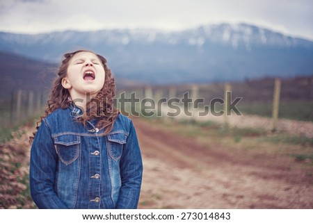 Little girl in nature yelling - stock photo
