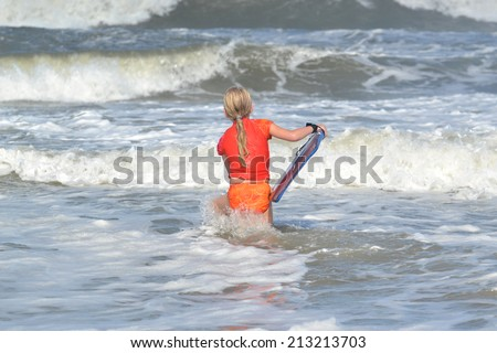 little girl in ocean ready to surf waves - stock photo