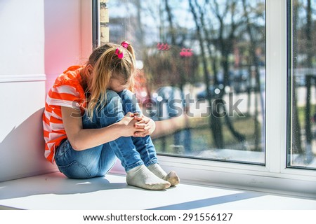 Little girl in orange blouse sits on a window sill, crying. - stock photo
