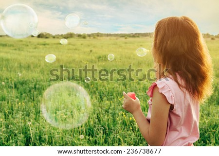 Little girl in pink dress blowing soap bubbles on summer meadow at sunny day, rear view. Image with sunlight effect - stock photo