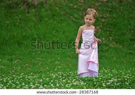 Little girl in pink dress on the grass - stock photo
