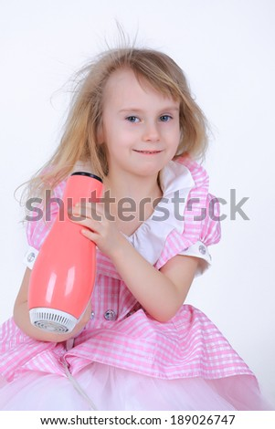 Little girl in pink dress with a hairdryer doing her hair isolated on white in studio - stock photo