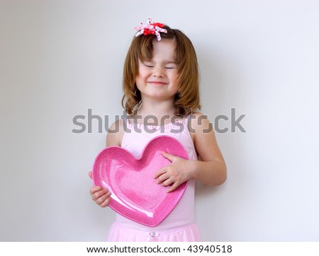 Little girl in pink holding a heart over the light background - stock photo