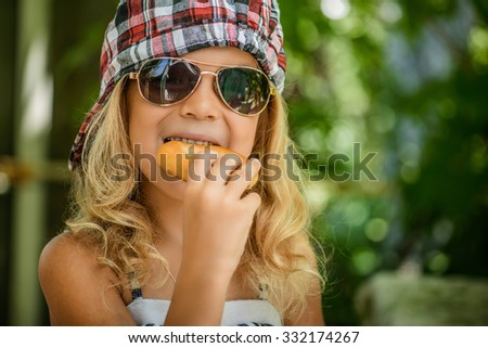 Little girl in plaid cap and sunglasses eating bagel against green of Park in summer. - stock photo
