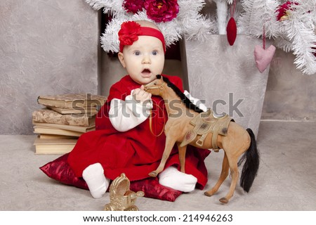 Little girl in red dress near Christmas tree with a toy horse. Baby 5 months. Christmas, New Year - stock photo