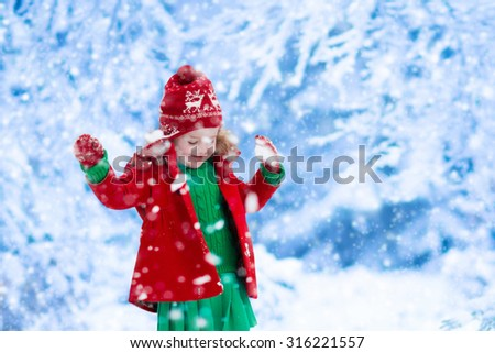 Little girl in red jacket and green knitted dress catching snowflakes in winter park on Christmas eve. Kids play outdoor in snowy winter forest. Children catch snow flakes on Xmas. Toddler kid playing - stock photo