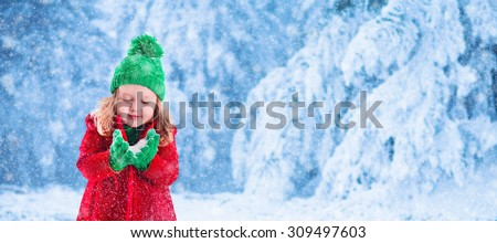 Little girl in red jacket and green knitted hat catching snowflakes in winter park on Christmas eve. Kids play outdoor in snowy winter forest. Children catch snow flakes on Xmas. Panorama banner - stock photo