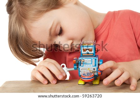 little girl in red T-shirt plays with clockwork robot isolated on white background - stock photo