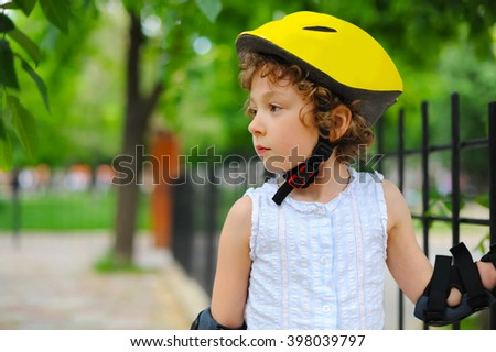 Little girl in roller skates and helmet in park at summer. Pretty child, kid riding a roller. Close-up portrait of cheerful preschool girl wearing roller skates and protective equipment. - stock photo