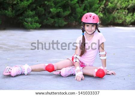 Little girl in roller skates at  park - stock photo