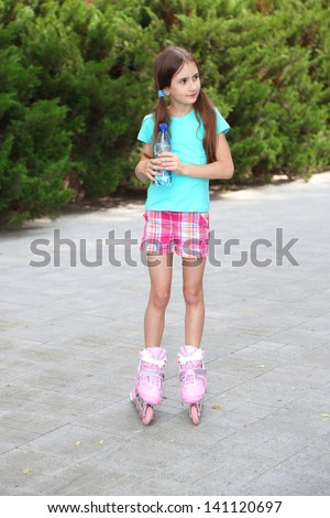 Little girl in roller skates drinking water at  park - stock photo