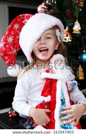 Little girl in santa claus hat - stock photo