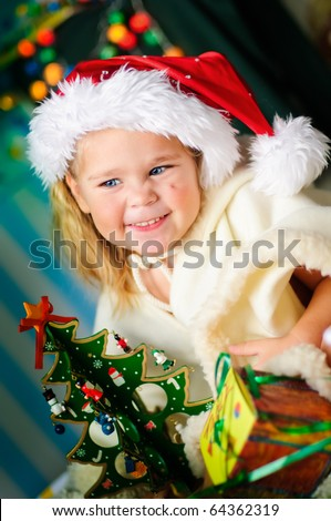 little girl in santa hat with gift and christmas tree smiling - stock photo