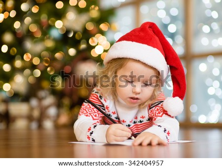 little girl in Santa hat writes letter to Santa Claus - stock photo