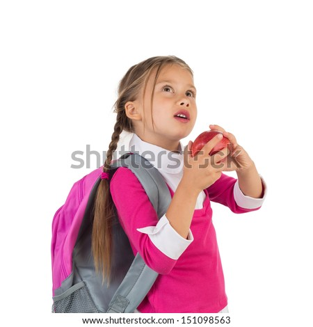 Little girl in school uniform looking up wistfully and holding an apple, isolated - stock photo