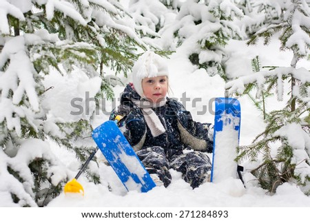 little girl in skiing sits on the snow in the forest - stock photo