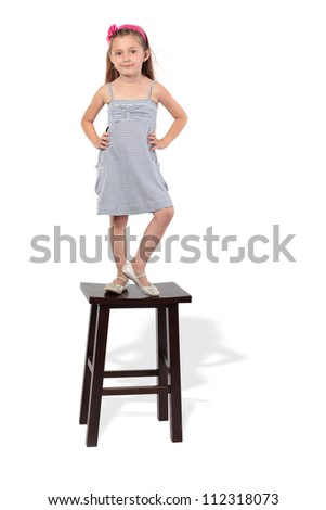 Little girl in striped dress stands on stool - stock photo