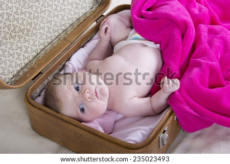 little girl in suitcase	. one month baby girl in a vintage suitcase - stock photo