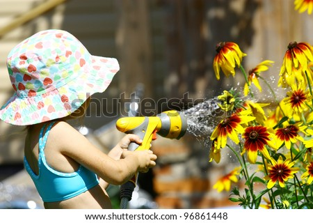 Little girl in summer hat watering yellow flowers - stock photo