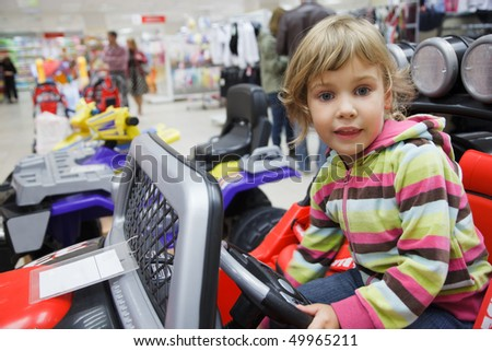 little girl in supermarket alone, chooses in department of toys. sits in an electromobile - stock photo