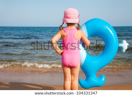 little girl in swimsuit looks at the sea and holds an inflatable toy - stock photo