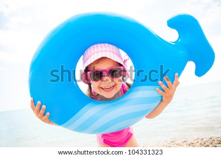 little girl in swimsuit playing with an inflatable whale on the beach resort - stock photo