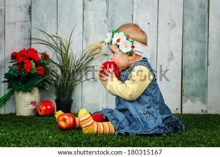 Little girl in the backyard sits on a lawn and eats an apple - stock photo