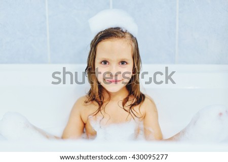 little  girl in the bathroom playing with foam  - stock photo