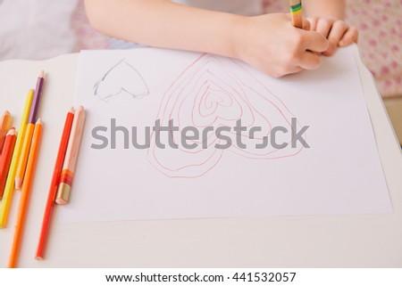 little girl in the bedroom. pretty little girl draws. girl woke up. girl draws heart. girl and pencils. - stock photo