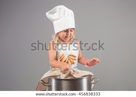 Little girl in the clothes chef hat and apron to cook a delicious meal in a large pot in a studio on a gray background - stock photo