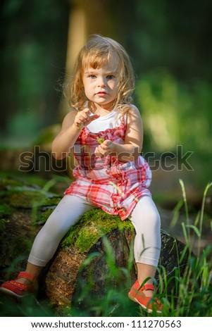 Little girl in the dark green forest - stock photo
