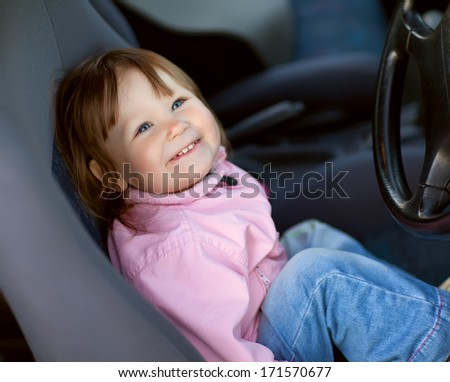 Little girl in the driver's seat of a car - stock photo