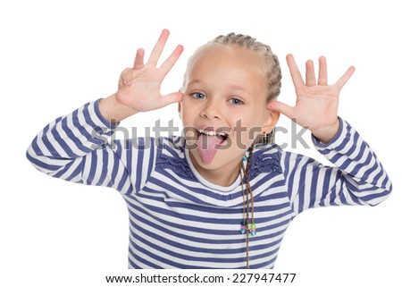 Little girl in the form of a sailor boy jokingly stuck out her tongue. Girl is six years old. - stock photo