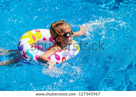 little girl in the pool  with rubber ring - stock photo