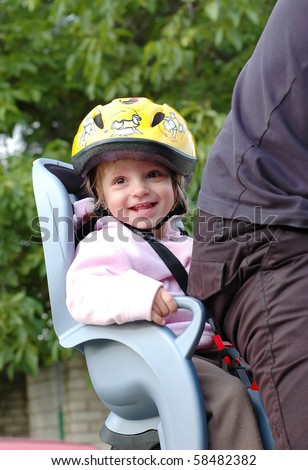 Little girl in the seat bicycle with a helmet on his head - stock photo