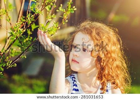 Little girl in the spring park, background toning for instagram filter. - stock photo