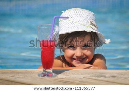 Little girl in the swimming pool with cocktail - stock photo