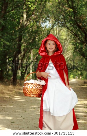 "Little girl in the wood looks up. the fairy tale "" Red Riding Hood"" - stock photo"
