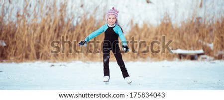 little girl in thermal suits skating  outdoors - stock photo